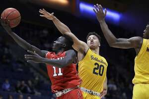 Utah's Both Gach, left, lays up a shot past California's Matt Bradley (20) and Darius McNeill in the second half of an NCAA college basketball game Saturday, Jan. 26, 2019, in Berkeley, Calif. (AP Photo/Ben Margot)