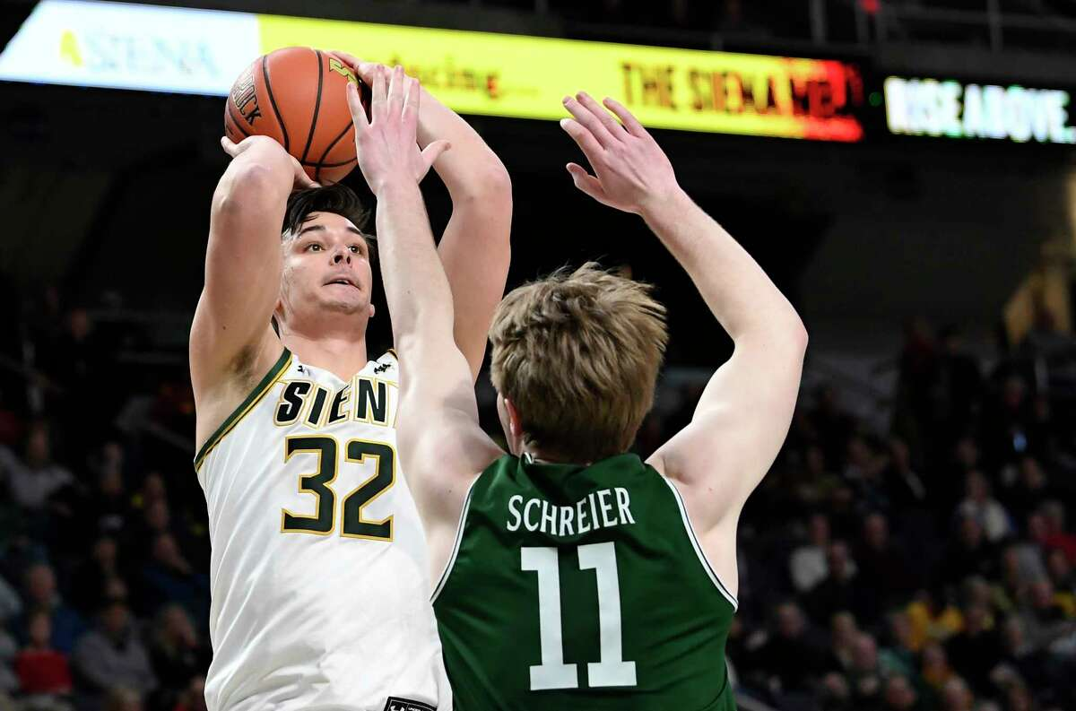 Siena forward Evan Fisher (32) shoots the ball over Manhattan forward Daniel Schreier (11) in the first half of a Metro Atlantic Athletic Conference NCAA college basketball game, Saturday, Jan. 26, 2019, in Albany, N.Y.