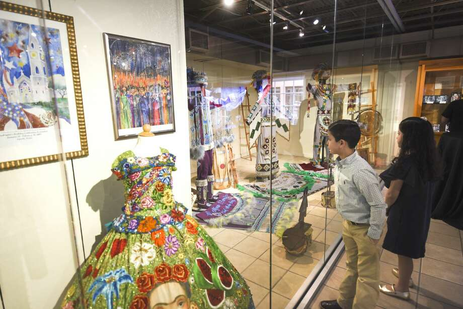 D.B. Hastings and Luisa Gabriela Garcia look through the previous Princess Pocahontas Pageant and Society of Martha Washington dresses during the opening of the WBCA Museum on Friday, Jan. 25, 2019, at the WBCA Museum. Photo: Danny Zaragoza/Laredo Morning Times