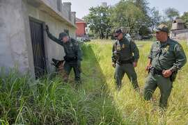 A border patrol dog sits in front of a locked steel door where three immigrants are hiding from CBP agents in the backyard of a home in Roma, Texas, about a block north of the Rio Grande, in August 2018. (Robert Gauthier/Los Angeles Times/TNS)