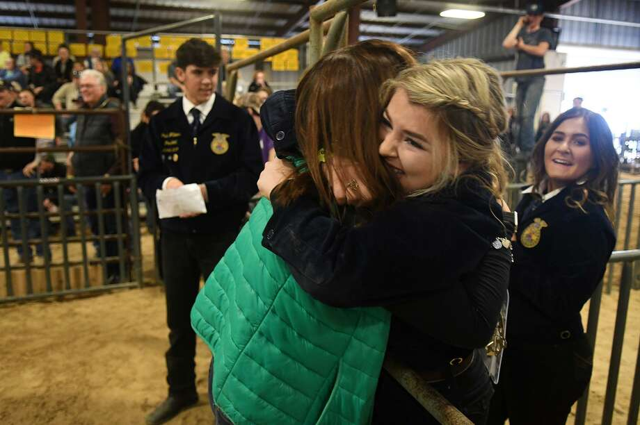 Molly McEachern, 17, center, a senior at Tomball Memorial High School, gets a hug from Natalie Ludwig, left, after McEachern's brother Max, 15, a THS freshman, won first in his class after Molly won first in her class during the Tomball ISD FFA Goat Show at Tomball High School on Jan. 25, 2019. Max ultimately won Grand Champion Runner-up and Molly placed third in the judging. Photo: Jerry Baker, Houston Chronicle / Contributor / Houston Chronicle