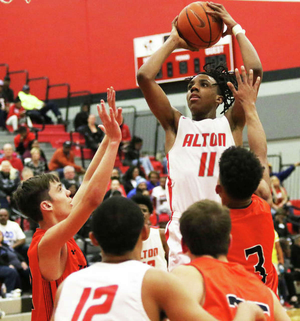 Alton's Donovan Clay (11) rises up in the lane for a shot over Edwardsville defenders during the Redbirds' Southwestern Conference victory on Tuesday at Alton High in Godfrey. The Redbirds were in Galesburg on Saturday and Clay scored 23 points in a shootout win over Rock Island.