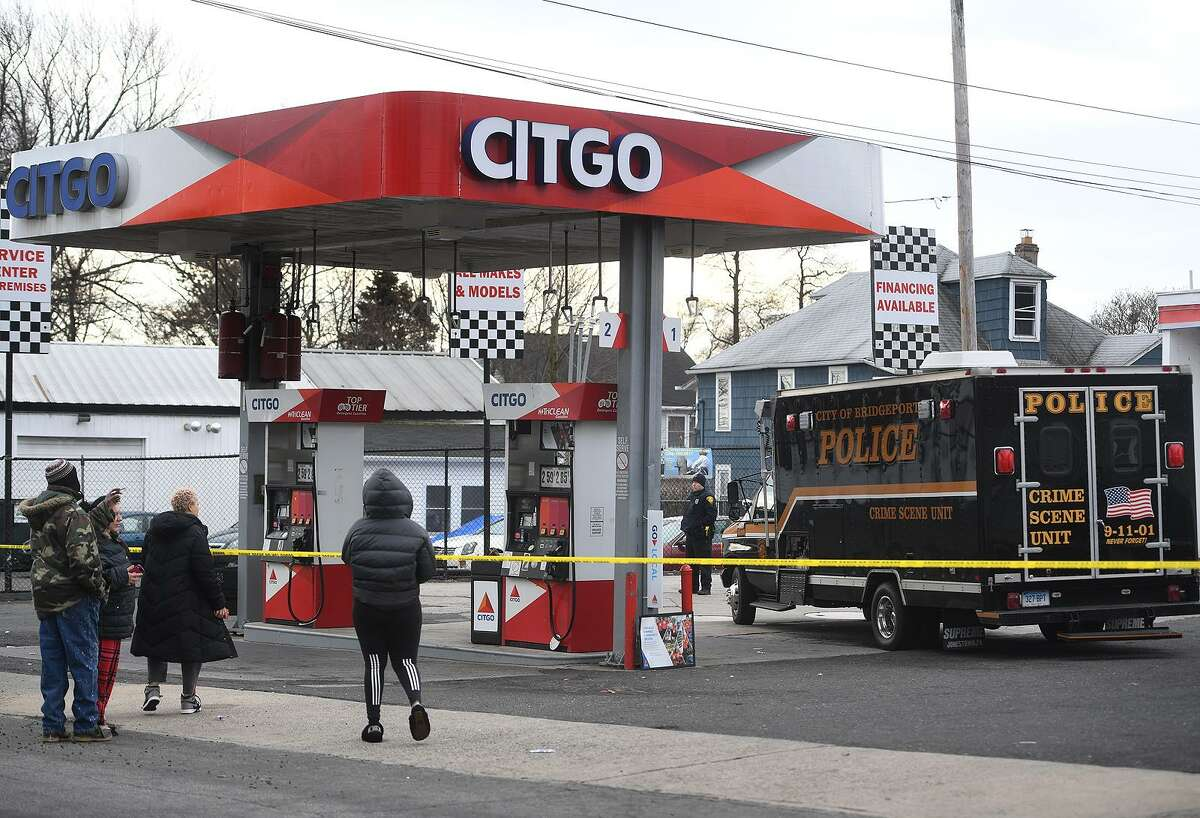 With relatives of the deceased looking on behind a perimeter of police tape, Bridgeport police investigate a homicide at the Citgo service station at 915 Reservoir Avenue in Bridgeport, Conn. on Sunday, January 27, 2019.