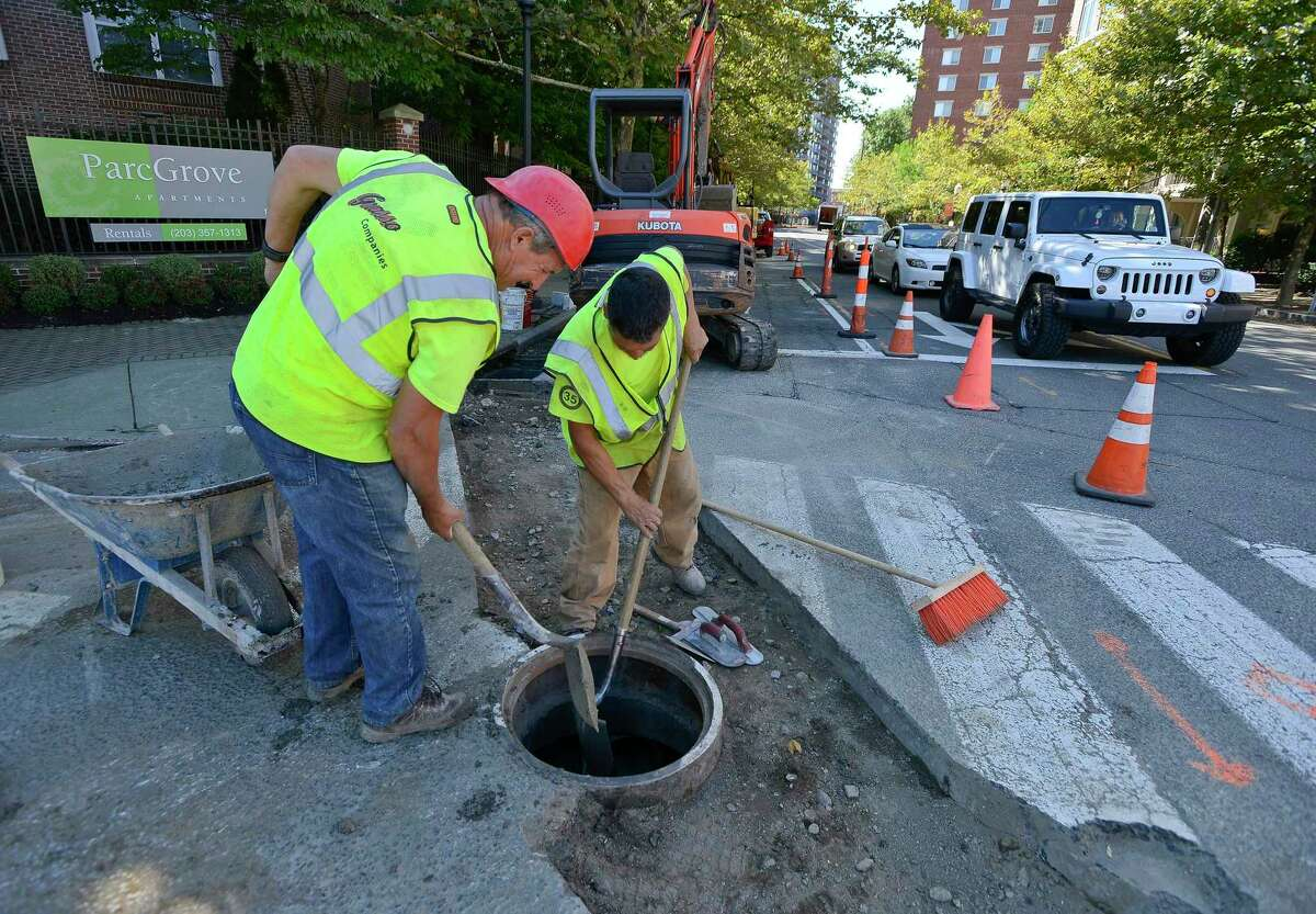 """Martin Farias and Domingos Daerira of Grasso Companies, Norwalk, CT, finish repairs to a 12"""" storm drain at the corner of Forest and Grove Street in Stamford on Sept. 22, 2017."""