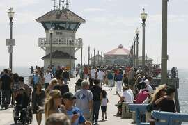 """FILE - In this Sept. 5, 2011, file photo, pedestrians walk along the Huntington Beach Pier in Huntington Calif. California Gov. Gavin Newsom's administration is using a new law for the first time in an attempt to force Southern California's self-styled """"Surf City USA"""" to meet housing goals. The administration on Friday, Jan. 25, 2019, said it is suing Huntington Beach under the law that took effect Jan. 1. The measure was passed in 2017 as part of a package of bills intended to address the state's severe housing shortage and homelessness problem. (Armando Brown/The Orange County Register via AP, File)"""