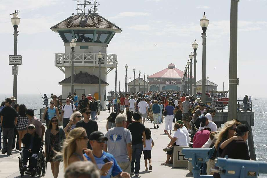 "FILE - In this Sept. 5, 2011, file photo, pedestrians walk along the Huntington Beach Pier in Huntington Calif. California Gov. Gavin Newsom's administration is using a new law for the first time in an attempt to force Southern California's self-styled ""Surf City USA"" to meet housing goals. The administration on Friday, Jan. 25, 2019, said it is suing Huntington Beach under the law that took effect Jan. 1. The measure was passed in 2017 as part of a package of bills intended to address the state's severe housing shortage and homelessness problem. (Armando Brown/The Orange County Register via AP, File) Photo: Armando Brown / Associated Press 2011"