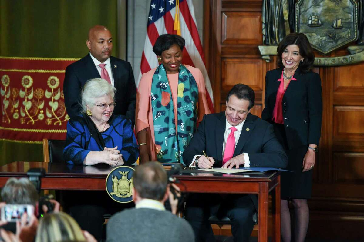 Former Gov. Andrew Cuomo signs the Reproductive Health Act on Jan. 22, 2019. From left: Assembly Speaker Carl Heastie (standing), Sarah Weddington (sitting), State Senate Majority Leader Andrea Stewart-Cousins, Cuomo and Gov. Kathy Hochul.