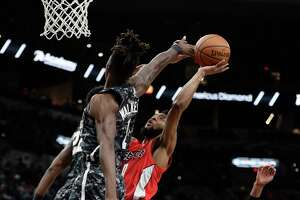 Washington Wizards guard Chasson Randle (9) drives to the basket against San Antonio Spurs guard Lonnie Walker IV (1) during the first half of an NBA basketball game in San Antonio, Sunday, Jan. 27, 2019. (AP Photo/Eric Gay)