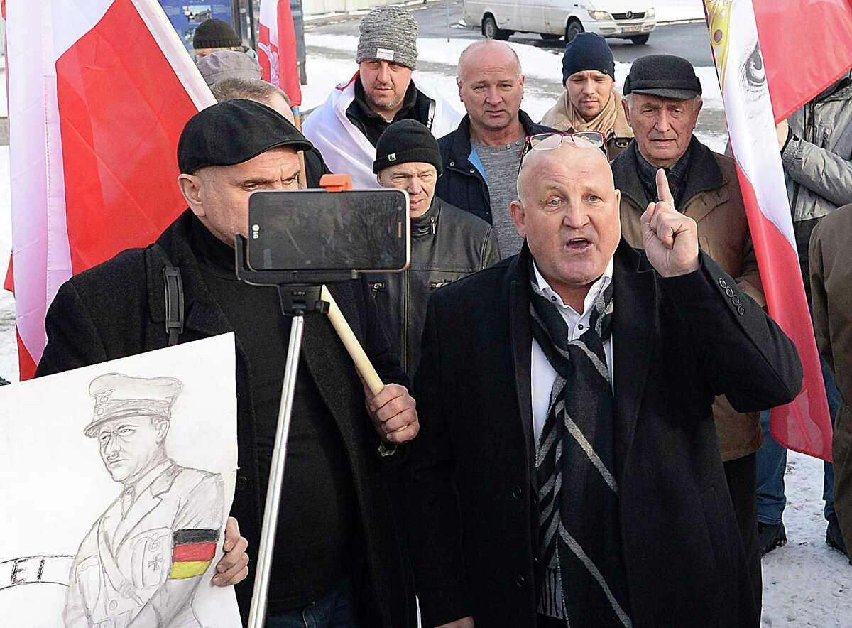 A Polish far-right activist, Piotr Rybak,right, and other nationalists gather outside the memorial site of Auschwitz in Oswiecim, Poland, on Sunday Jan. 27, 2019. Rybak has been imprisoned for burning the effigy of a Jew. He said his gatherings Sunday was an act of protest against the Polish government, which he accuses of remembering only Jews and not murdered Poles in yearly observances at the memorial site.(AP Photo/Czarek Sokolowski)