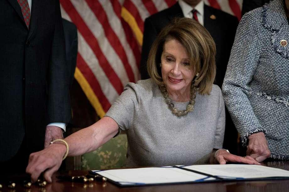 La presidenta de la Cámara de Representantes Nancy Pelosi (D-Calif.) firma un proyecto de ley para reabrir el gobierno federal en el Capitolio, Washington, el viernes. El plan no incluye dinero para un muro fronterizo y fue esencialmente el mismo enfoque que rechazó el presidente Donald Trump en diciembre, lo que significa que no concretó nada durante el callejón sin salida. (Erin Schaff / The New York Times) Photo: ERIN SCHAFF /NYT / NYTNS