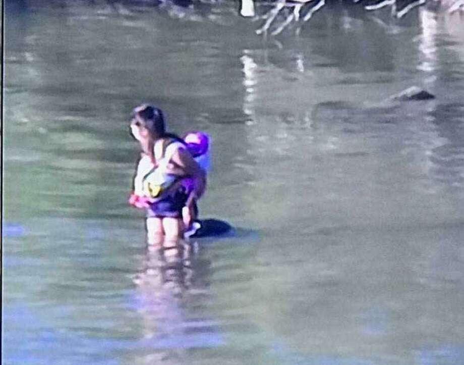 La mujer hondureña se encontraba en medio del rio, esperando asistencia para ella y si hijo de 10 meses tras haber sido abandonados. Photo: Foto De Cortesía: BPD /