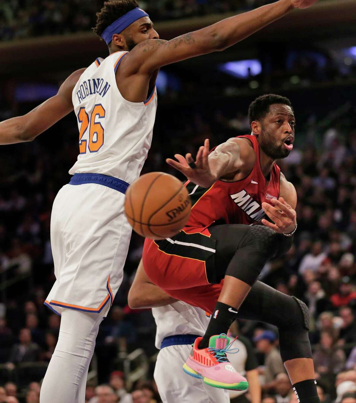 Miami Heat's Dwyane Wade, right, passes around New York Knicks' Mitchell Robinson during the first half of the NBA basketball game, Sunday, Jan. 27, 2019, in New York. (AP Photo/Seth Wenig)