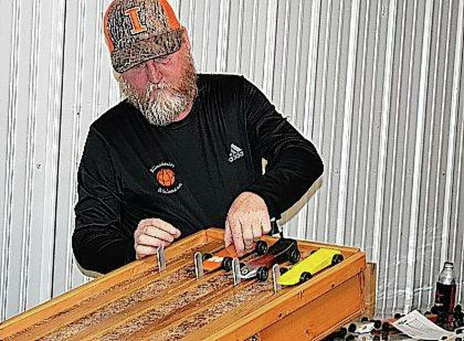 Jeff Spencer prepares cars for the first run of the Adult Pine Car Derby on Saturday at the Jacksonville Speedway. The event benefited the Ken Bradbury Foundation. Photo: Samantha McDaniel-Ogletree | Journal-Courier