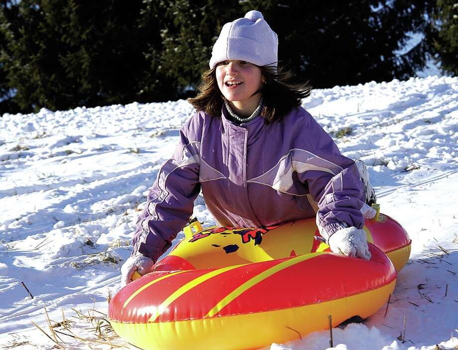Emily Fazzino, 8, of Portland faces the cold wind boldly as she rides her snow tube down a hill behind Riverdale Motel on Monday...photo by Theresa Aresco...122704 Photo: Middletown Press File Photo