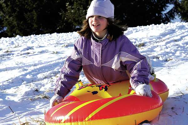 Emily Fazzino, 8, of Portland faces the cold wind boldly as she rides her snow tube down a hill behind Riverdale Motel on Monday...photo by Theresa Aresco...122704