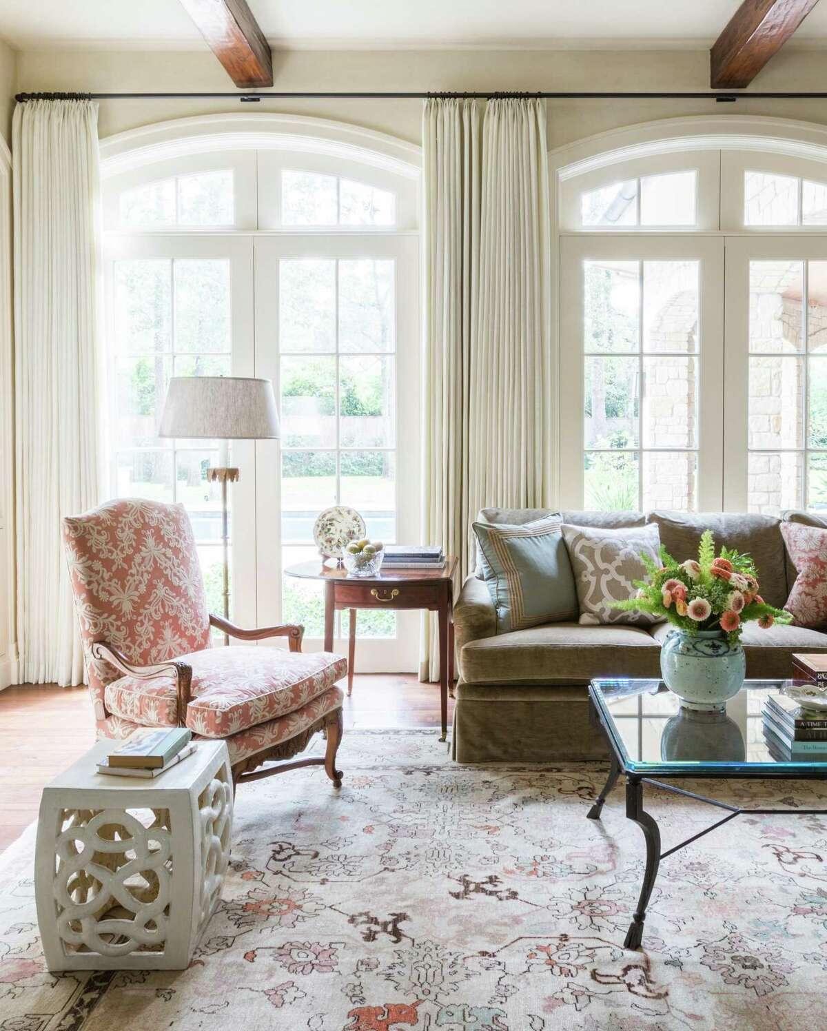 Off white draperies against off white walls help soften this large family room designed by Sarah Eilers of Lucas Eilers Design Associates.