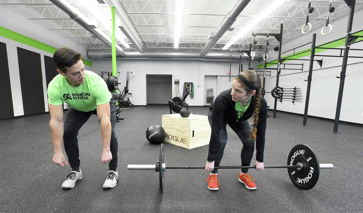 Craig DeCollibus, a co-owner of Stateline Fitness in Greenwich, Connecticut and his wife Christine DeCollibus demonstrate what clients might expect when working with an instructor one on one at their recently opened new strength and conditioning facility on Friday, Jan. 25, 2019.