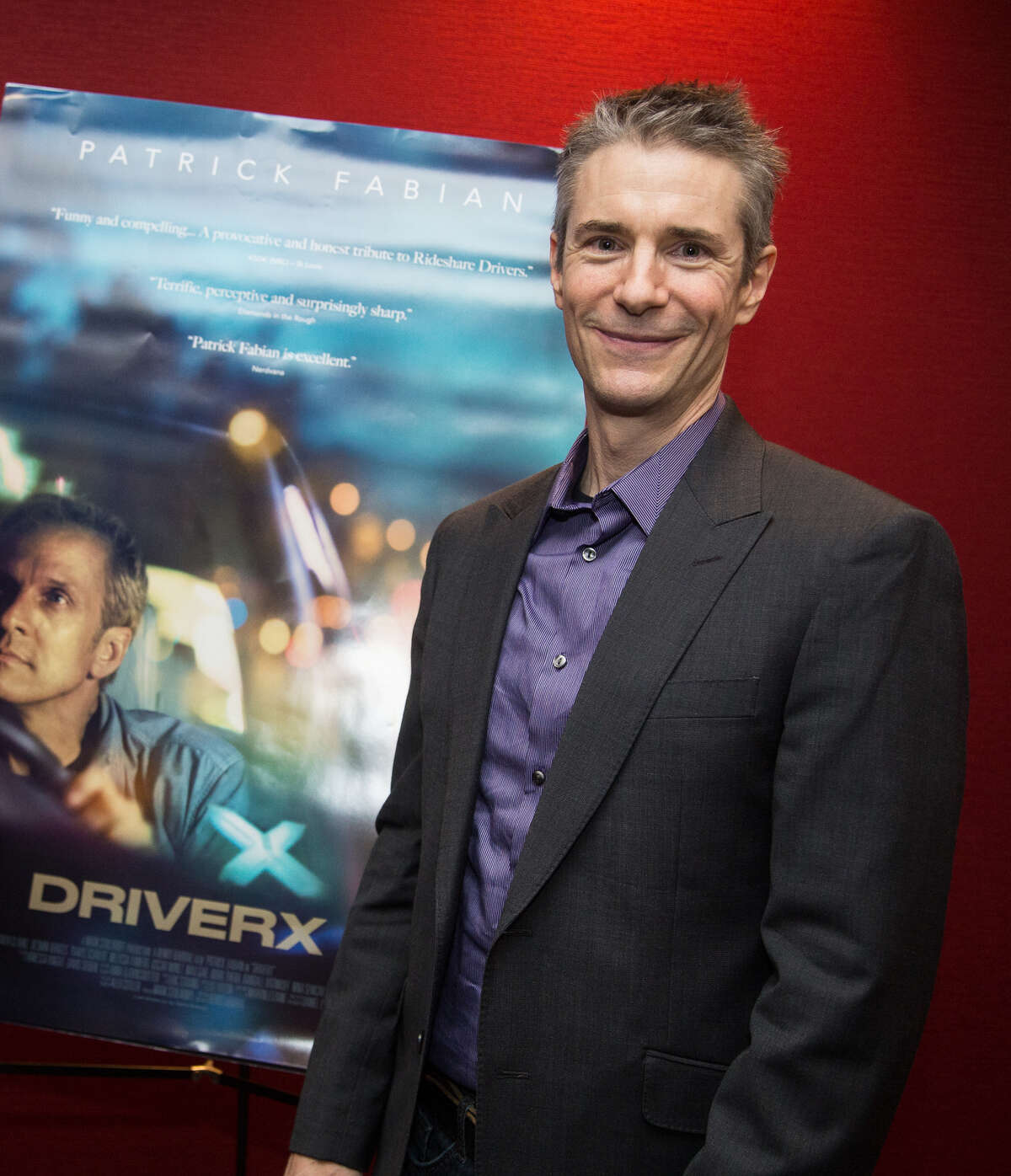 Producer Mark Stolaroff in front of poster for his film