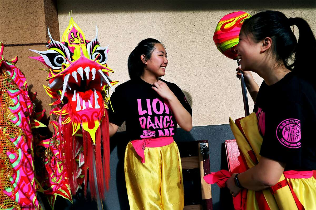 Alyson Wong, 14, and Joanna Chen, 14, members of LionDanceME, converse following their performances at Macy's Center Court at Hillsdale Mall in San Mateo, Calif., on Saturday, January 26, 2019.