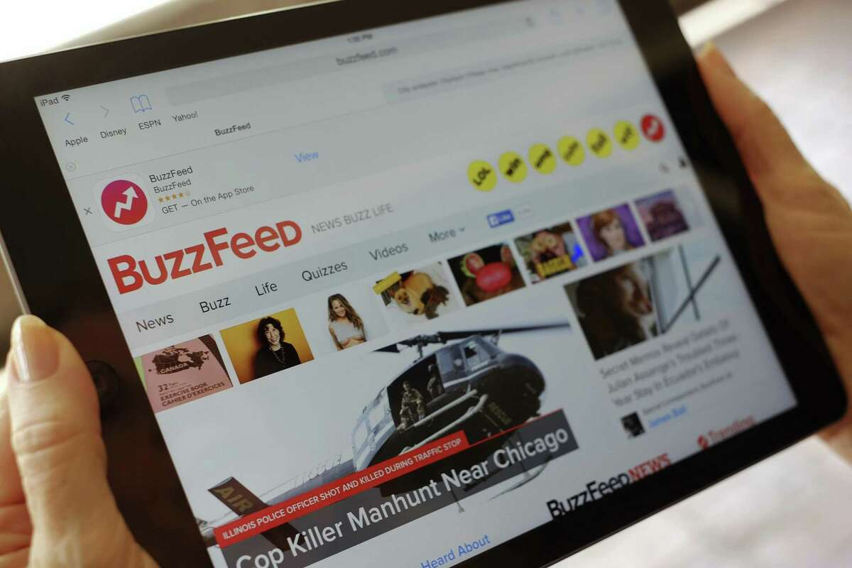 In this Sept. 2, 2015, file photo the BuzzFeed website is displayed on an iPad held by an Associated Press staffer in Los Angeles. Media company BuzzFeed is cutting 15 percent of its jobs, or about 200 people, to trim costs and become profitable. BuzzFeed CEO Jonah Peretti said in a memo to employees Jan. 23 that the layoffs will help BuzzFeed avoid having to raise money from investors again.