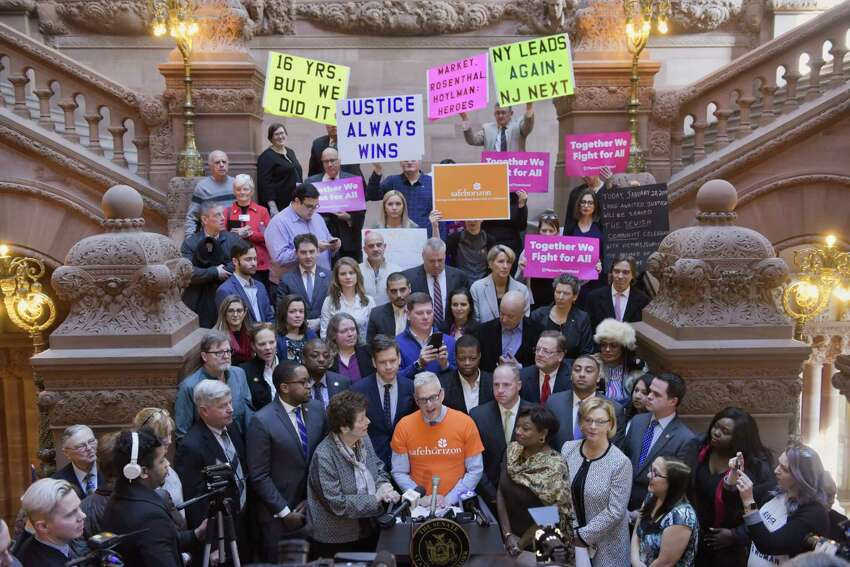 Michael Polenberg, at podium, Vice President, Government Affairs, Safe Horizon, surrounded by child sex-abuse survivors, advocates and members of the Assembly and Senate, celebrates the impending passage of the Child Victims Act, during an event at the Capitol on Monday, Jan. 28, 2019, in Albany, N.Y. (Paul Buckowski/Times Union)