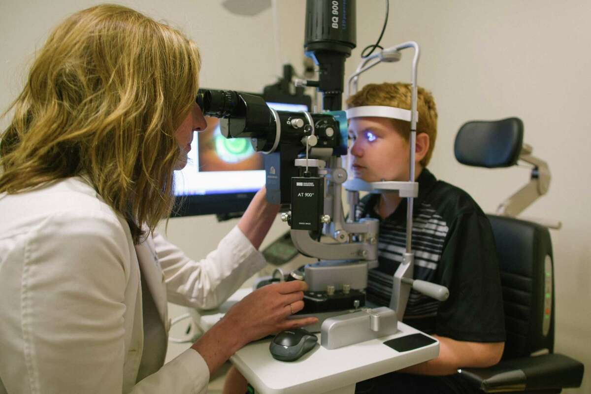 Kathryn Richdale, UH associate professor and optometrist at the University Eye Institute examines 12-year old Joaquin Martinez, a patient of the University's Myopia Management Service.