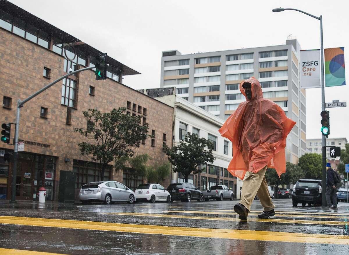 A man sports a bright orange rain poncho while crossing Polk Street in San Francisco, Calif. Tuesday, Jan. 15, 2019.