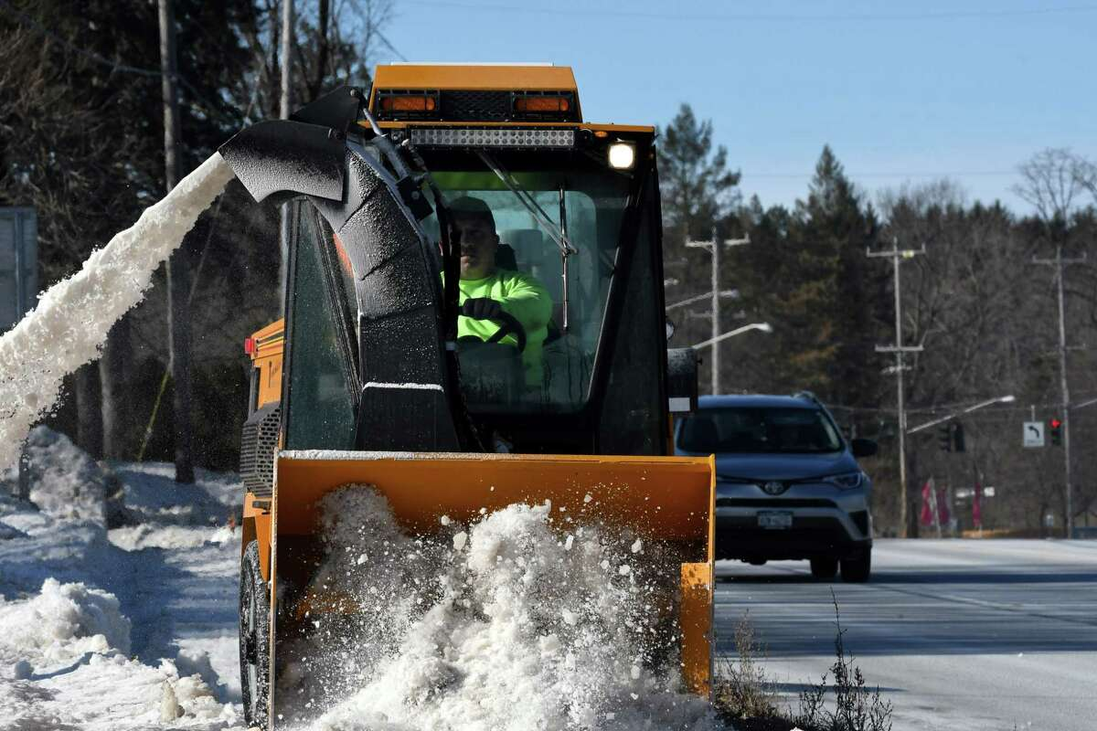 Snow is cleared from the sidewalk along Troy Schenectady Road by a Town of Niskayuna Highway Department worker on Monday, Jan. 28, 2019, in Niskayuna, N.Y. Between 4-8 inches of snow are expected to fall beginning on Tuesday. (Will Waldron/Times Union)