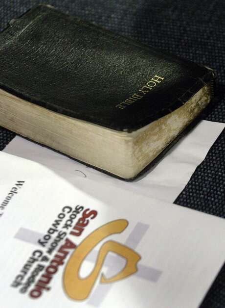 An old Bible rests on a chair next to printed material about the Cowboy Church at the San Antonio Stock Show & Rodeo.