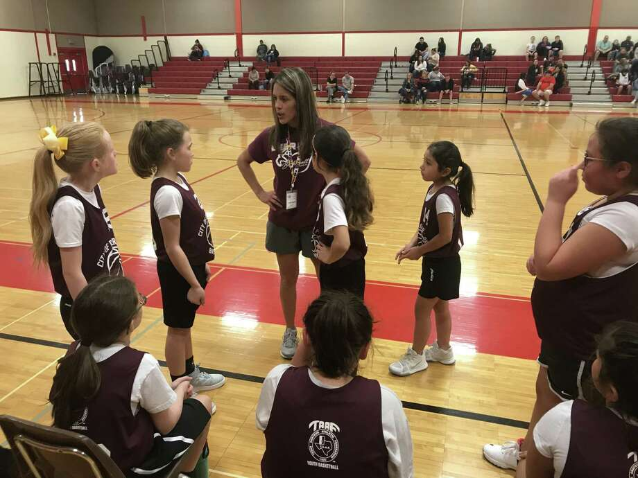 How can a referee call fouls on basketball players with ponytails and sweet dispositions? Some of those kind of players listen to their coach just before taking the court for the second half Saturday. Photo: Robert Avery