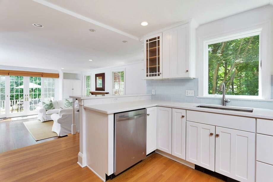The fully renovated kitchen at 87 West Ave. has white quartz countertops, white cabinets, stainless steel appliances and a window looking out to the side yard. Photo: Halstead Connecticut