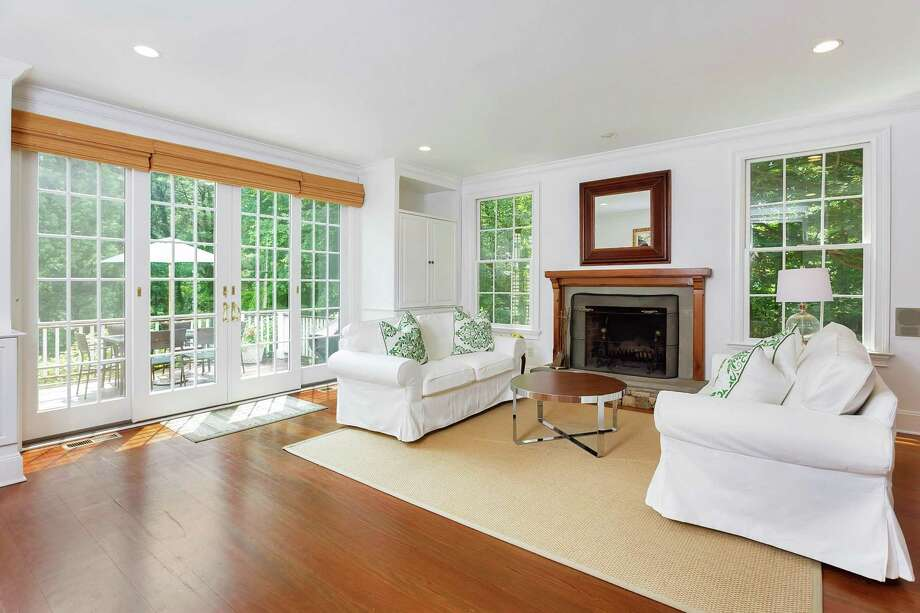 The family room at 87 West Ave. in Darien was added during a 2010 expansion and features a cherry wood floor, wood-mantled fireplace, sliding French doors to the backyard and high ceilings. The renovated 1890 farmhouse is listed for $1.194 million. Photo: Halstead Connecticut