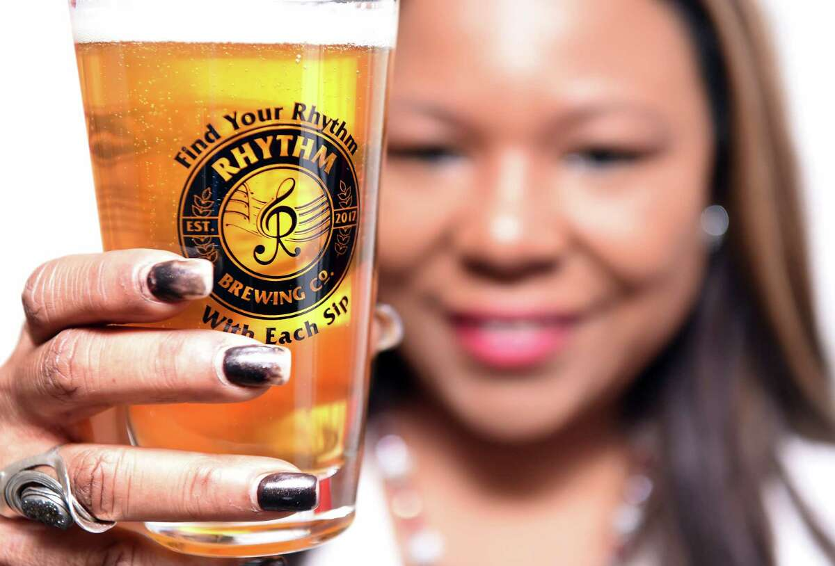 Alisa Bowens-Mercado, owner of Rhythm Brewing Company, holds a glass of Rhythm Unfiltered Lager beer at her other business, Alisa's House of Salsa, in New Haven on January 28, 2019.