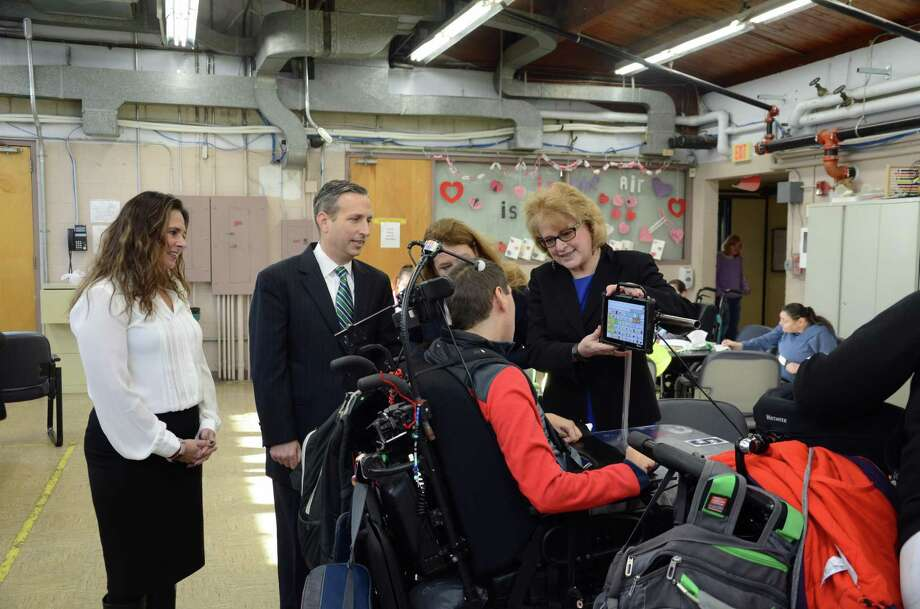 STAR staff and state legislators engage with a client's assistive technology. Photo: Tatiana Flowers / Hearst Connecticut Media / Norwalk Hour