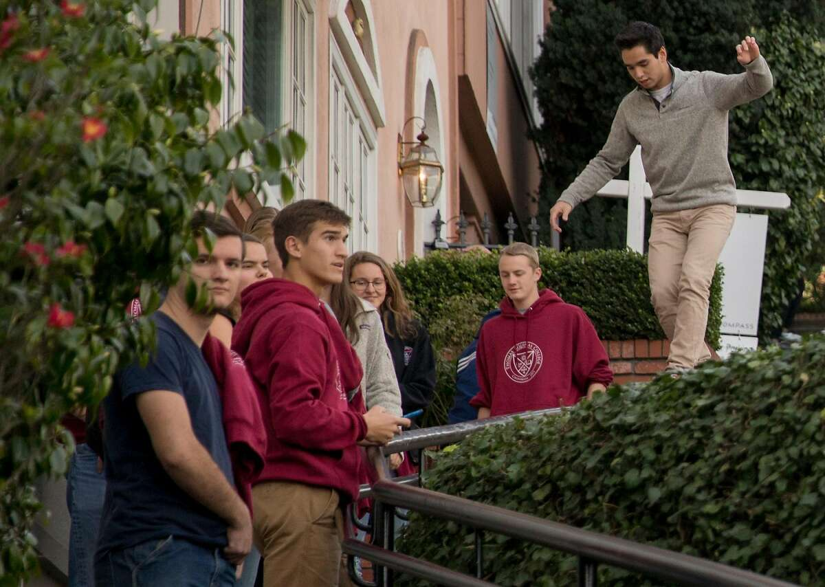 Tourists climb on private walls while walking along the famously crooked portion of Lombard Street in San Francisco, Calif. Saturday, Jan. 26, 2019.
