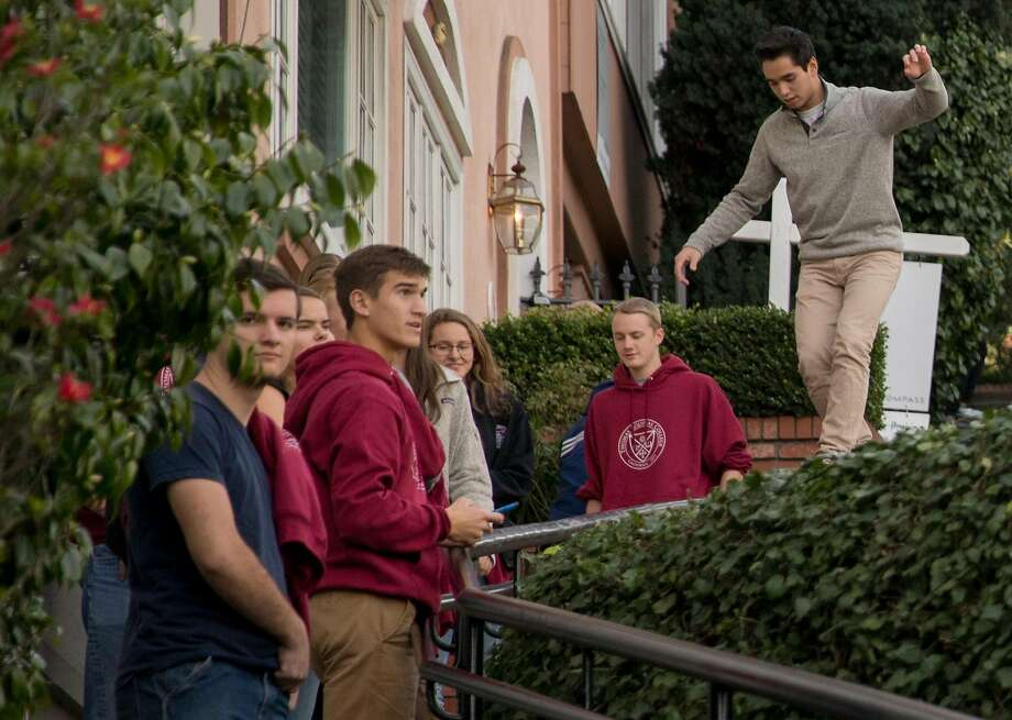 Tourists climb on private walls while walking along the famously crooked portion of Lombard Street. Photo: Photos By Jessica Christian / The Chronicle