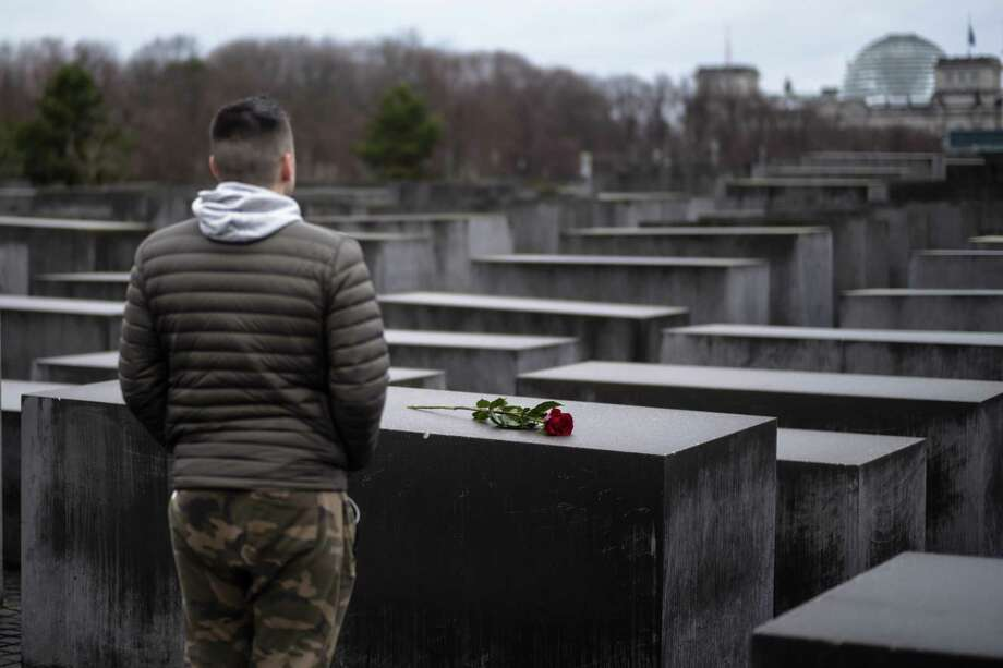 A young man stands in front of the Holocaust Memorial after he laid down a red rose on a slab of the memorial to commemorate the victims of the Nazis in Berlin, Sunday, Jan. 27, 2019. The International Holocaust Remembrance Day marks the liberation of the Auschwitz Nazi death camp on Jan. 27, 1945. (AP Photo/Markus Schreiber) Photo: Markus Schreiber / Associated Press / C-Markus Schreiber