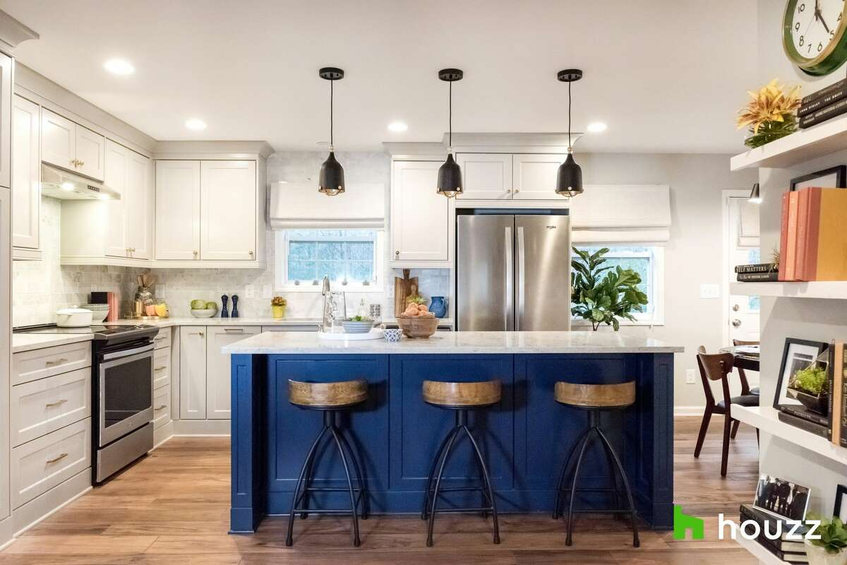 After: Now, the kitchen is magazine ready, with a dark blue island, bright white cabinets and new flooring. In fact, everything in the main living area -- breakfast nook, kitchen and living room -- is new.