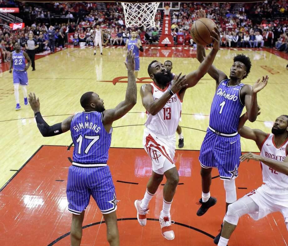 Houston Rockets guard James Harden (13) drives to the basket as Orlando Magic forwards Jonathon Simmons (17) and Jonathan Isaac (1) defend during the first half of an NBA basketball game, Sunday, Jan. 27, 2019, in Houston. Photo: Eric Christian Smith, FRE / Associated Press / Copyright 2019 The Associated Press. All rights reserved.