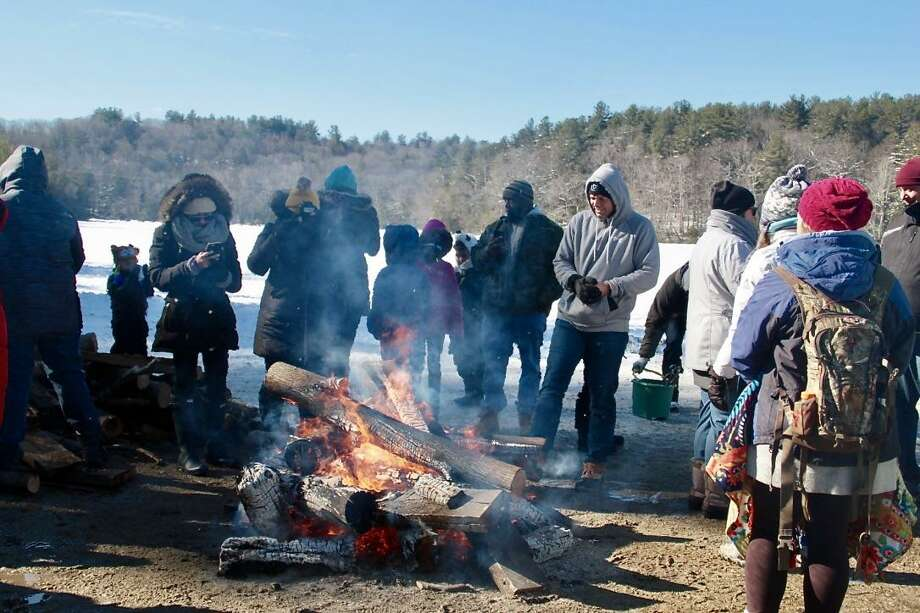 The annual Connecticut Department of Energy and Environmental Protection's No Child Left Inside annual free Winter Festival will be held Saturday, Feb. 2, 2019 at Burr Pond State Park in Torrington. Activities planned for the day included ice fishing, a fish fry, snowshoeing, ice sculpting and snow play, wildlife tracks, winter hikes, ice safety rescue demonstrations by the Torrington Fire Department, LL Bean and BASS Pro demos, visits from Resources in Search and Rescue and the Wolfpack Mascot, winter games, a marshmallow roast, bonfire and storytelling. Above, guests enjoy the bonfire at the 2018 event. Photo: Anita Garnett / Hearst Connecticut Media