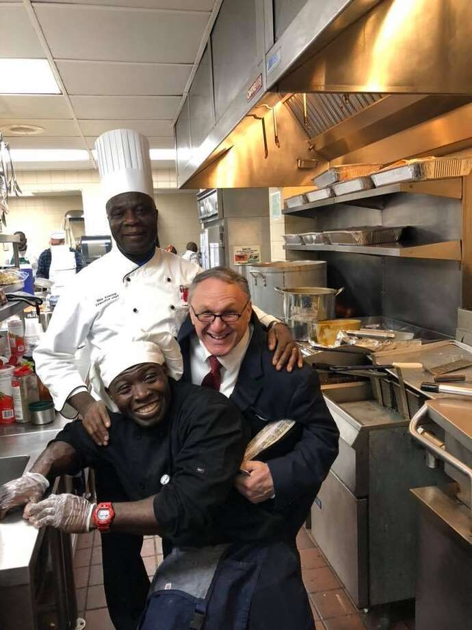 Kinimo Ngoran, chef at the Capital City Rescue Mission at the bottom left, poses for a picture in the kitchen with Perry Jones, executive director at the right, and Max Ansung, executive chef at the top left. Photo: Courtesy Of Capital City Rescue Mission