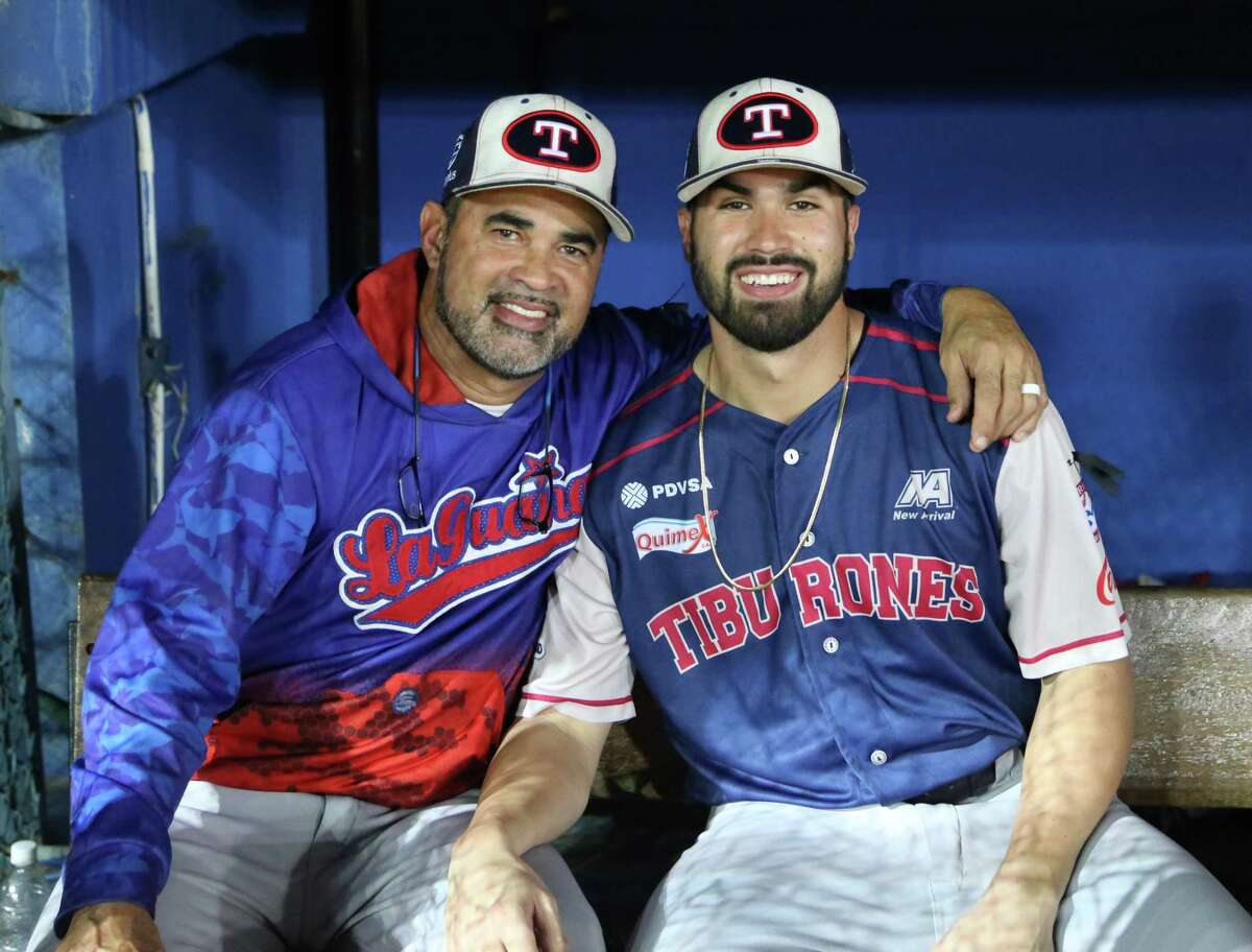 New Tri-City ValleyCats manager Ozney Guillen, right, sits with his father, former Chicago White Sox manager Ozzie Guillen. (Augusto Cárdenas / Cárdenas Sports Media)