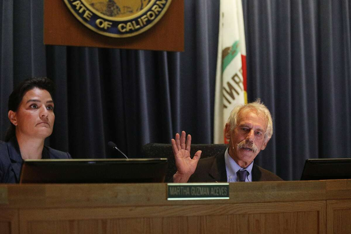 Michael Picker (right), president of the California Public Utilities Commission, gestures as he talks while demonstrators protest against a PG&E bailout during a previously unscheduled CPUC meeting on Monday, January 28, 2019 in San Francisco, Calif.