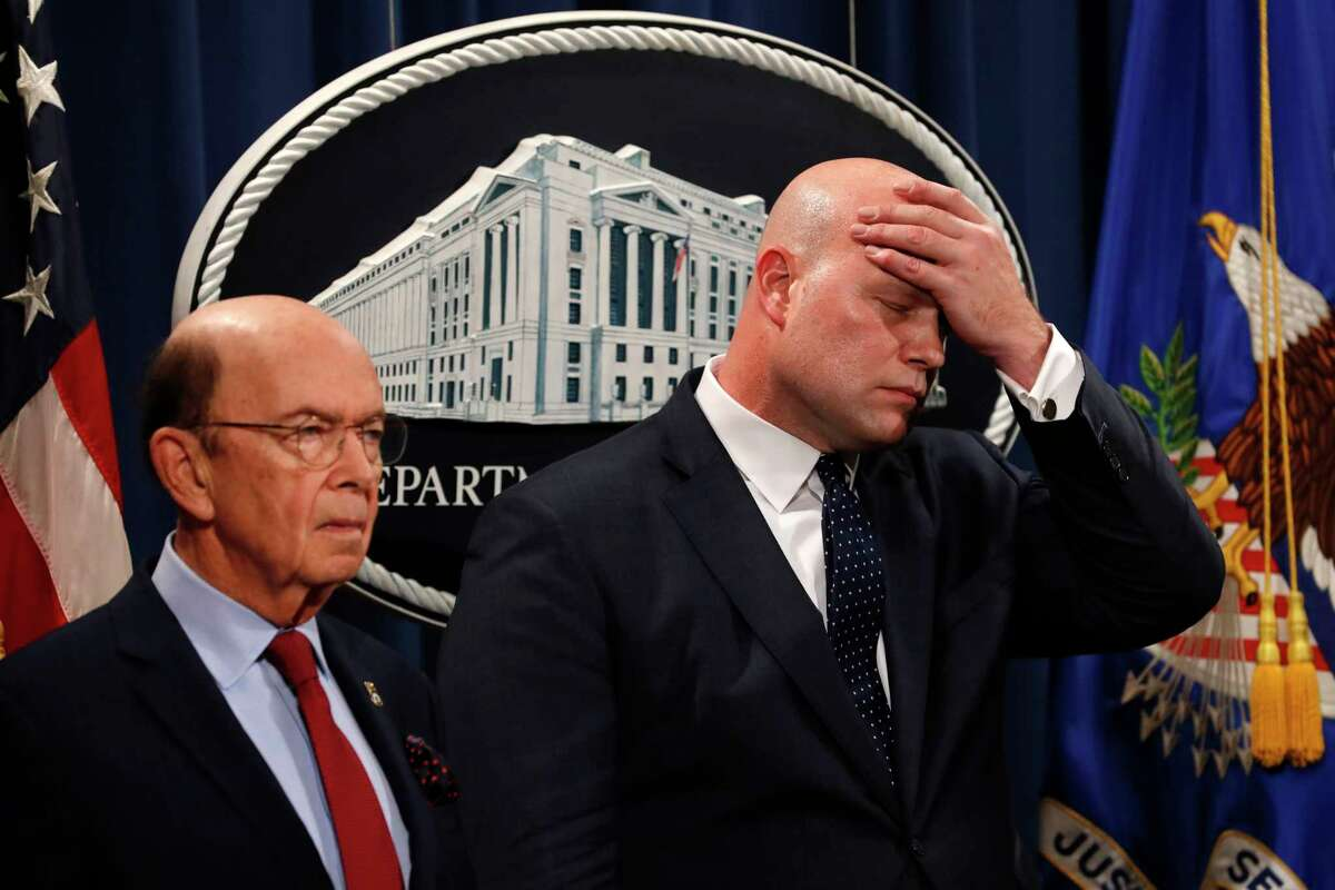 Acting Attorney General Matt Whitaker, right, wipes his brow after announcing an indictment on violations including bank and wire fraud, Monday, Jan. 28, 2019, of Chines telecommunications companies including Huawei, at the Justice Department in Washington. At left is Commerce Secretary Wilbur Ross. (AP Photo/Jacquelyn Martin)