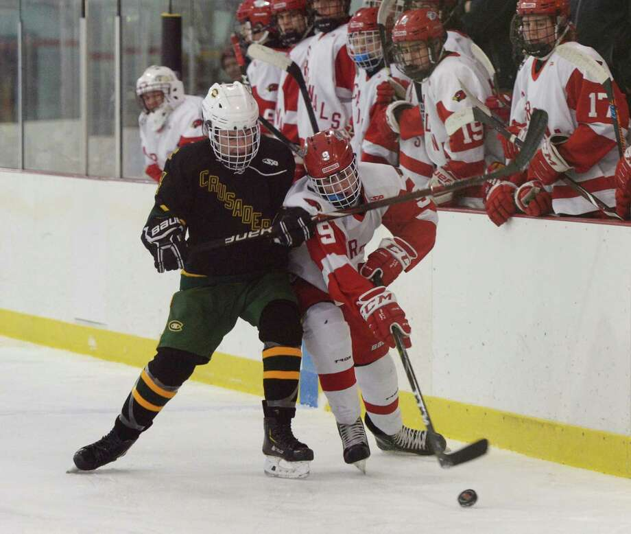Trinity Catholic's Jay Bacco (14) and Greenwich's Sean Duffy (9) battle against the boards in Greenwich's 7-0 win over Trinity Catholic in the high school boys ice hockey game at Dorothy Hamill Rink in Greenwich, Conn. Monday, Jan. 28, 2019. Photo: Tyler Sizemore / Hearst Connecticut Media / Greenwich Time