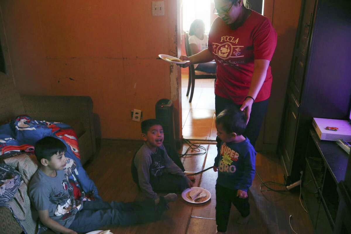 Crystal Guevara-Alvarado, 30, helps her youngest son, Joseph Sanchez, a 19-month-old, with his breakfast as he joins his stepbrothers, Ishmael Alvarado, 8, left, and Samuel Alvarado, 5. Guevara-Alvarado hopes to find new employment, perhaps with the Bexar County Sheriff's Office, she said.