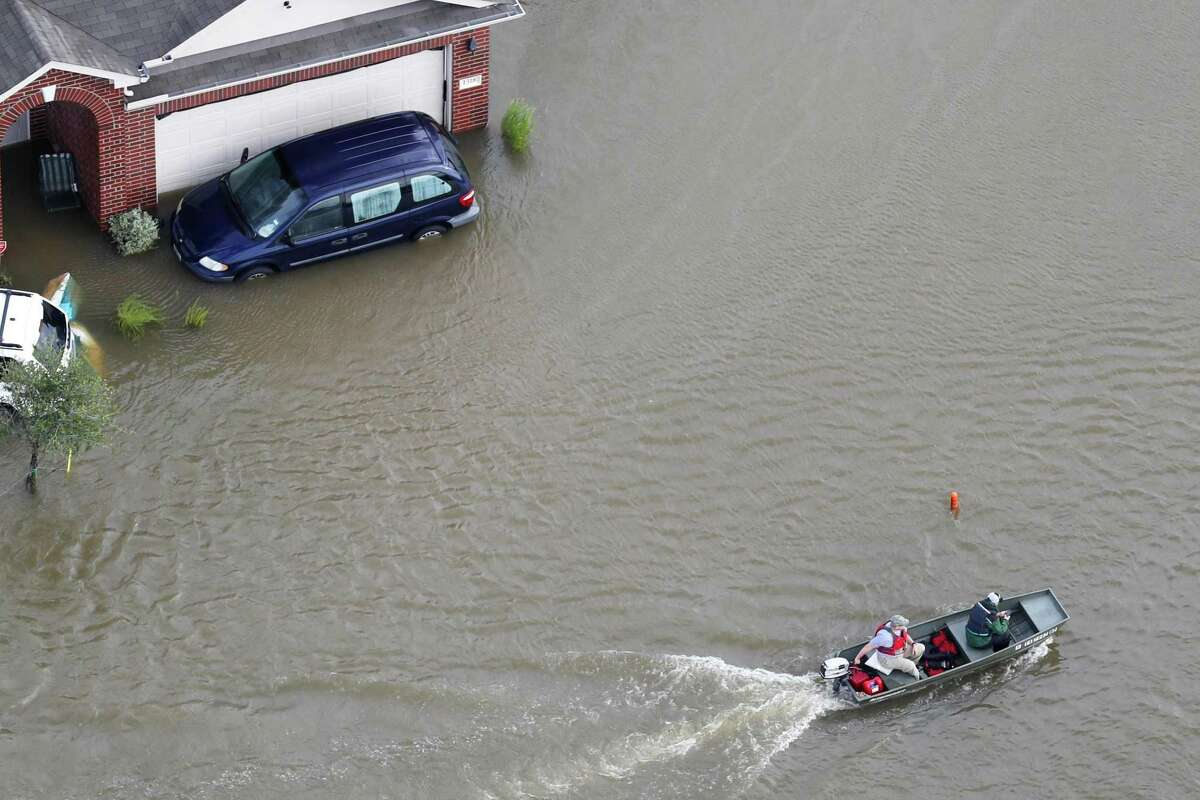 A boat runs past houses flooded by Hurricane Harvey on Tuesday, Aug. 29, 2017, in Spring.
