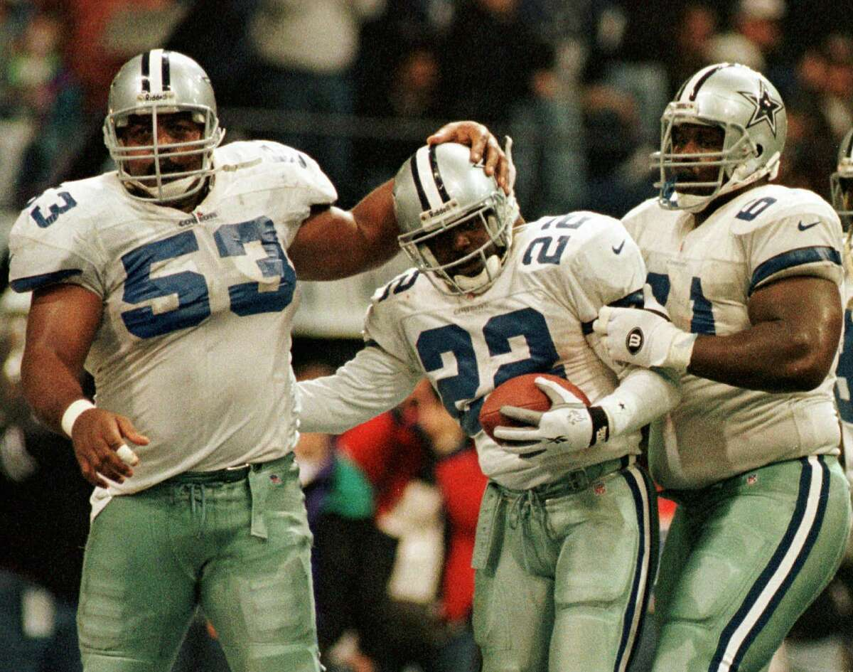 Dallas Cowboys running back Emmitt Smith (22) is congratulated by teammates Nate Newton (61) and Ray Donaldson (53) after he ran for a touchdown during the fourth quarter against the Washington Redskins in Irving, Texas, Thursday, Nov. 28, 1996. Smith ran for 155 yards. Dallas won 21-10. (AP Photo/Linda Kaye)