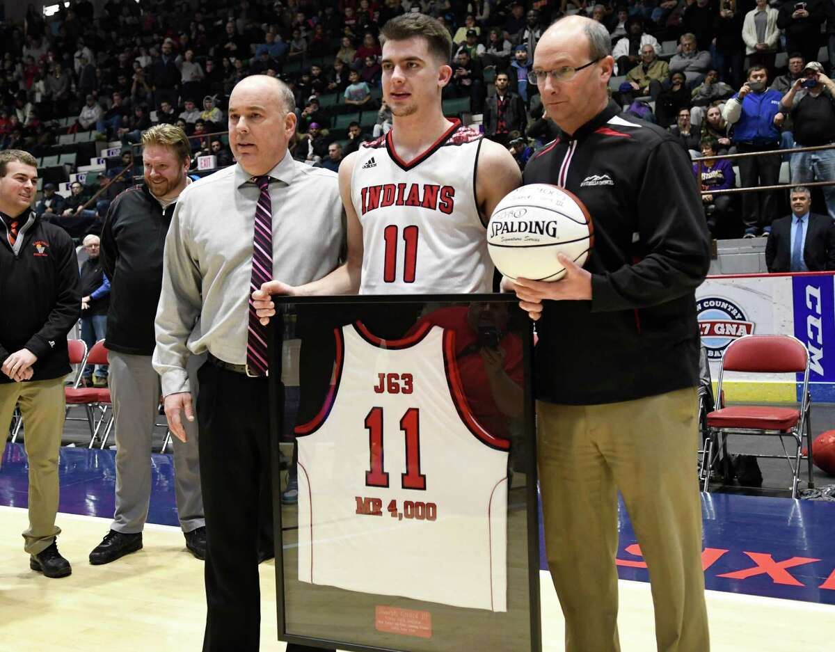 Glens Falls's Joe Girard III, center, poses with his coach, Rob Girard, left, and the Glens Falls High School Athletic Director after scoring his 4,000th career point at the Zero Gravity Slam North-South Classic in a game against Amsterdam at Cool Insuring Arena in Glens Falls, N.Y., on Sunday, Jan. 27, 2019. Girard became the sixth high school player in the country ever to score 4,000 career points. (Jenn March, Special to the Times Union)