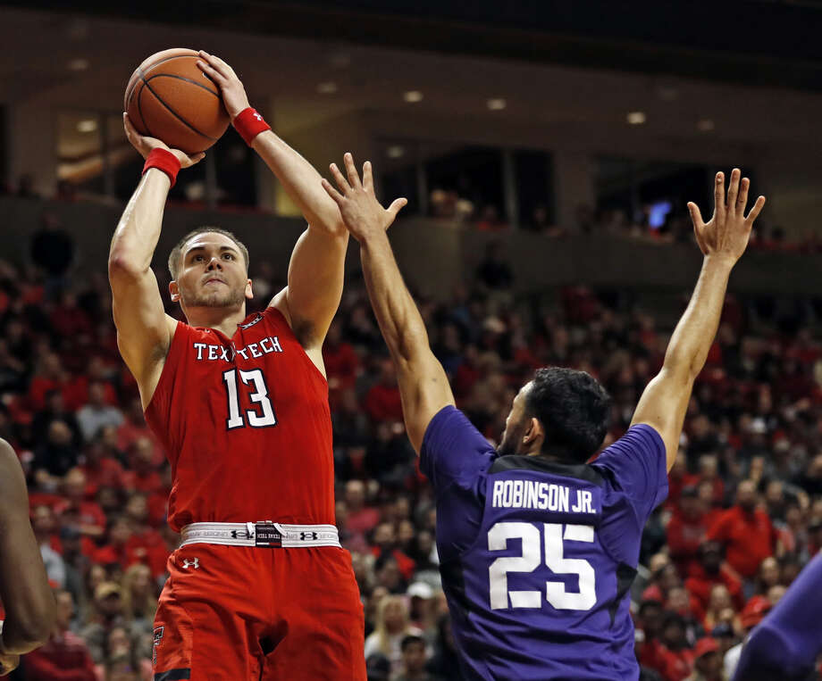 Texas Tech senior guard Matt Mooney lifts over TCU senior guard Alex Robinson's outstretched hands for a shot during Monday night's Big 12 Conference men's basketball game at United Supermarkets Arena in Lubbock. Photo: Brad Tollefson/Lubbock Avalanche-Journal